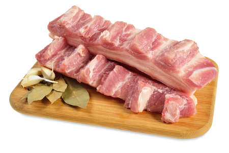 Raw bacon with ribs on a wooden cutting board  Isolated on white  Stock Photo