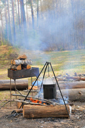 Camping kettle over burning campfire in the day light photo