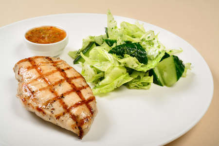 Grilled chicken breast with salad and sauce