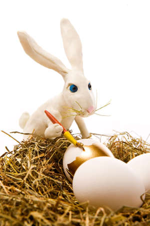 The white rabbit paints egg in gold colour in a nest photo