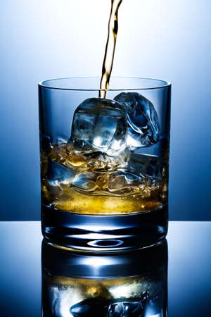 nightcap: Filling of a glass of whisky with ice