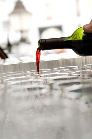 Red French wine pour from a bottle in the glasses which are standing in a row Stock Photo - 2888399