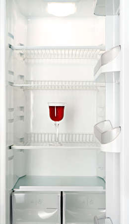 Red wine in a glass in an empty refrigerator photo