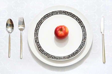 abstention: Red apple on a flat plate with a knife, a fork and a spoon Stock Photo