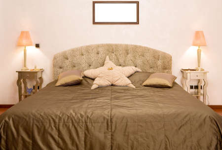 coverlet: Bedroom in which there is a big bed with a coverlet of olive colour, two little tables with lamps and a pillow in the form of a star