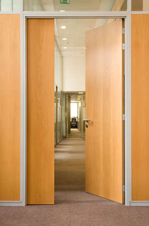 office interior design: The open door in a long corridor in which other open doors in office centre are visible