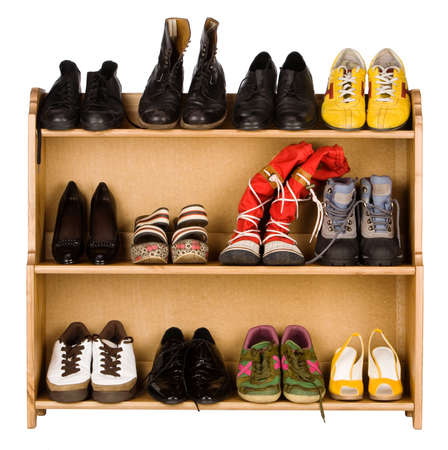 Shoes,  gym shoes, boots and other footwear stand on a rack Stock Photo