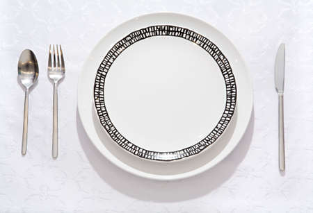deficiency: Empty pure plate on a table with an empty glass for wine, a spoon, a fork and a knife