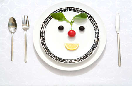 abstention: The meal made as a smiling face from olives, radish and lemon slice on a flat plate with a knife, a fork and a spoon Stock Photo