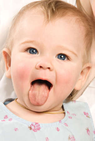 female tongue: The little girl in a blue dress shows out the tongue