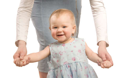 The smiling little girl in a blue dress hold on mum's hands and tries to go photo