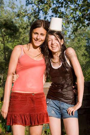 wet clothes: - Dos chicas adolescentes en ropa h�meda en un jard�n en el d�a de verano. La joven muchacha tiene un cubo blanco en la cabeza