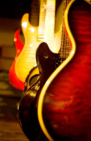 One acoustic guitar and some electric guitars stand nearby photo
