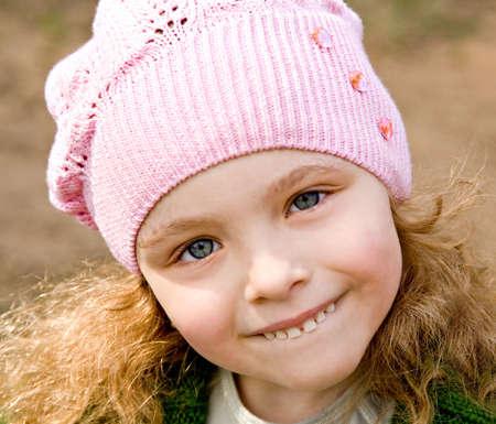 lepra: Retrato de la niña alegre en una tapa de color rosa con pelo largo