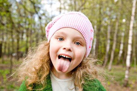 lengua afuera: Alegre ni�a en una rosa tapa pone la lengua a cabo en los bosques