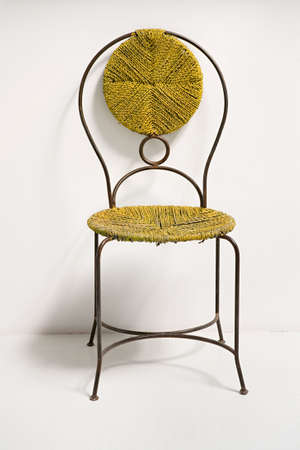The graceful chair with a wattled seat and a back stands near a wall photo