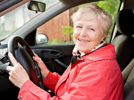 one senior adult woman: La sonriente mujer de edad avanzada en una chaqueta roja al volante del coche  Foto de archivo