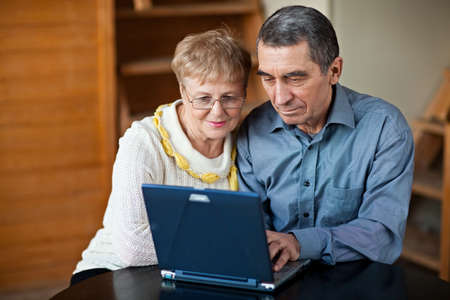 Old couple sitting together and using laptop photo