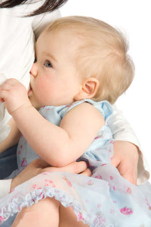 Baby girl sucking milk from mothers breast photo