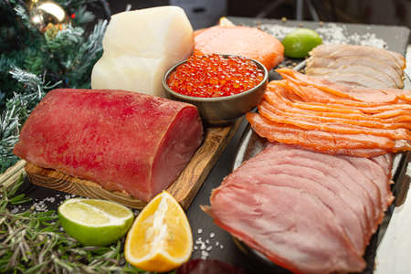 Caviar and smoked salmon sliced and in piece on a wooden board. Christmas and New Year background
