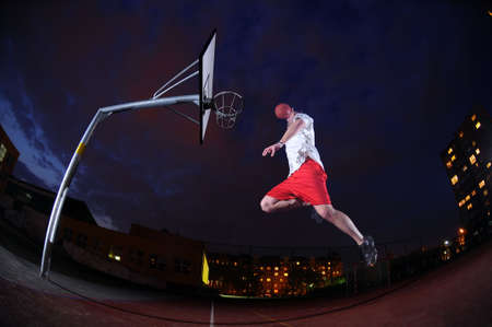 dunk: Basketball player slam dunking on an outdoor sports court Stock Photo