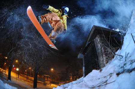 snowboarder jumping: Jumping snowboarder in the city at night in winter