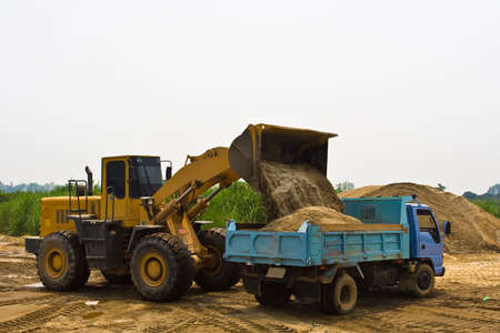 Working wheel loader with a truck in construction site.