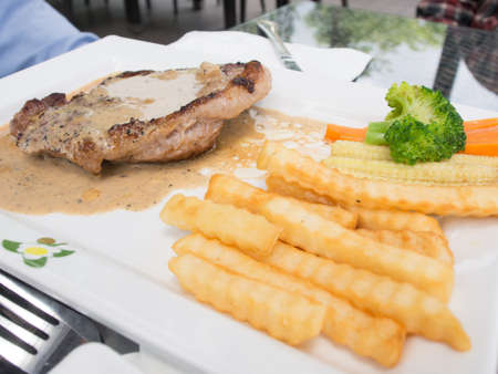 Pork stake in a white dish with vages and chips  Stock Photo - 16295060