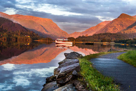 Lake in Llansberis in the dusk with with boat and mountain  Stock Photo