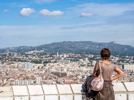 Single women looking at Marseille city view from high hill in a sunny day