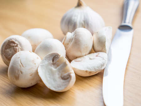 buttom: a group of Buttom mushroom, garlic, and a knife on wooden board