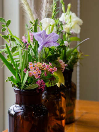 Lovely flowers and vase by a window. Stock Photo