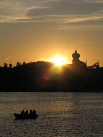 View of people in the boat at the  background silhouette of the city.(Pskov, Russia). photo