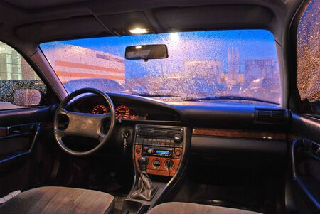 Evening. Rain. View of the car interior and parking near at market. photo