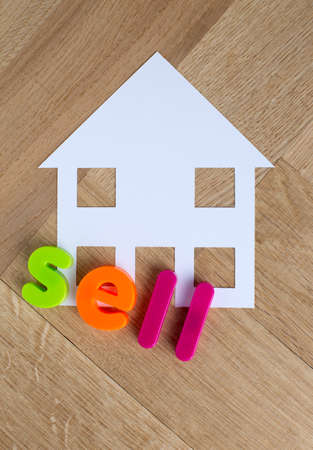 Sell house with house cut out on wooden floor with lettering spelling the word sell