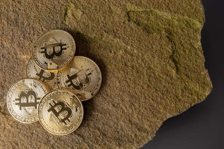 Bitcin group of gold coins resting on a rock on a grey background