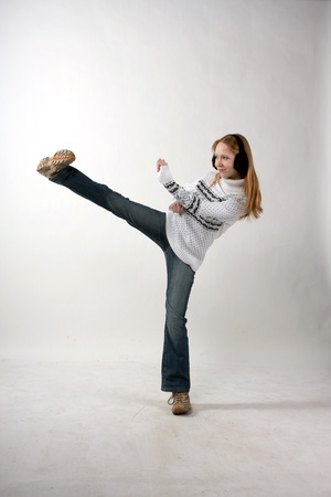 A young woman in jeans and a sweater kick photo