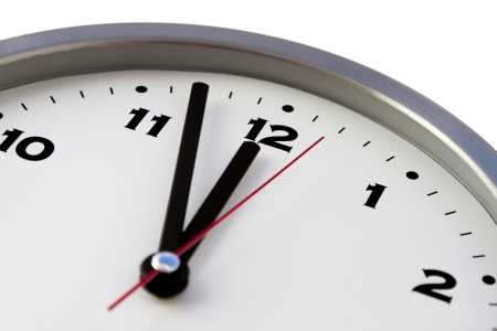 12 o'clock: 11 57 on the white wall clocks  isolated