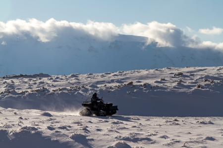 Man riding a quad bike on the snow mountains
