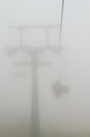 One of chair lifts in a ski resort in the fog