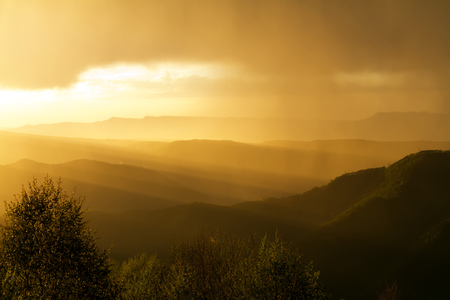 Gold suns rays at sunset in the thunderclouds of the mountains