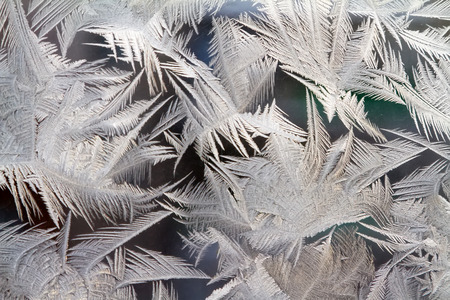 Frost draws abstract ice background patterns on a windowpane. Russia.