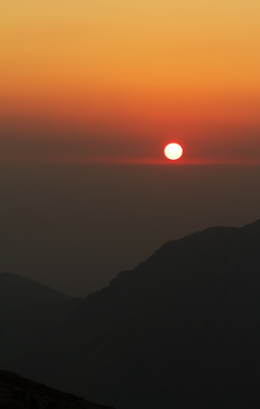 Red sunset over the mountains. Vertical landscape. Gradient Stock Photo