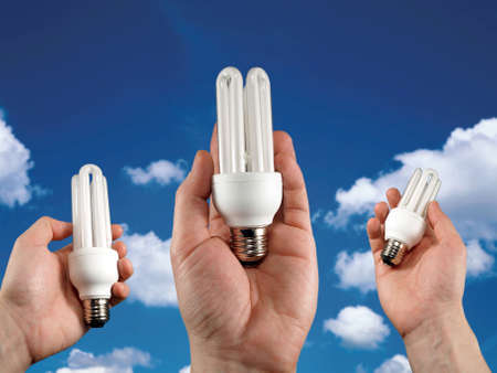 concept for energy saving. cf light bulbs in hands on sky background   Stock Photo - 4862568