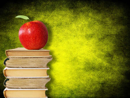 back to school concept. red apple on stack of books against painted wall background