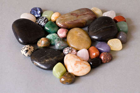 heart shape of colorful stones  on grey background photo