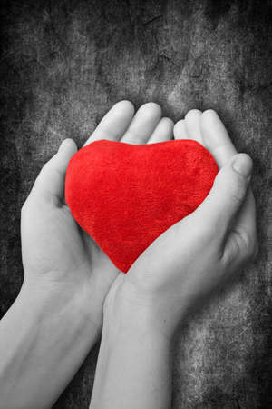 offerings: red heart in hands on dark background Stock Photo