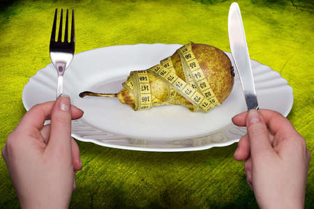 Health and diet concept.  hands holding fork and knife against pear  wrapped with  measure tape