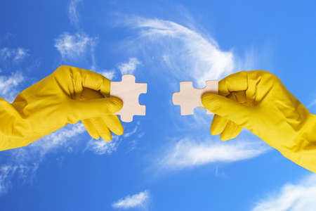 teamwork concept. hands with different pieces of puzzle on sky background photo