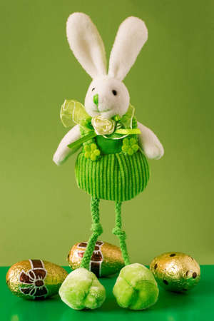 funny easter bunny and chocolate eggs on green background photo